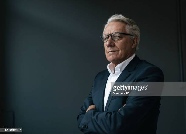 portrait of a senior businessman looking away - arme verschränkt stock-fotos und bilder