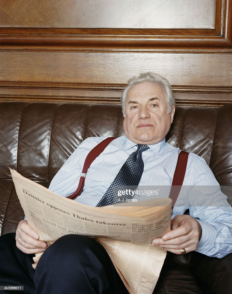 Portrait of a Senior Businessman Sitting on a Leather Sofa With a Newspaper : Stock Photo