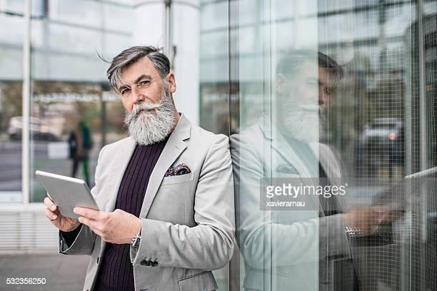 Portrait de Senior homme d'affaires à l'aide de tablette numérique