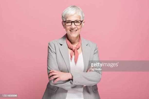 portret van een hogere onderneemster die glimlacht - roze achtergrond stockfoto's en -beelden