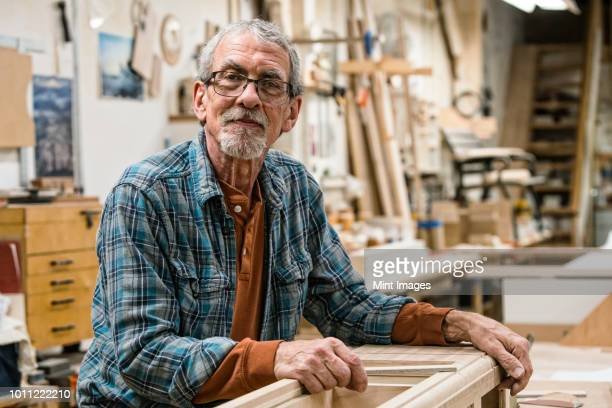 portrait of a senior caucasian carpenter in a large woodworking shop. - 65 69 anni foto e immagini stock