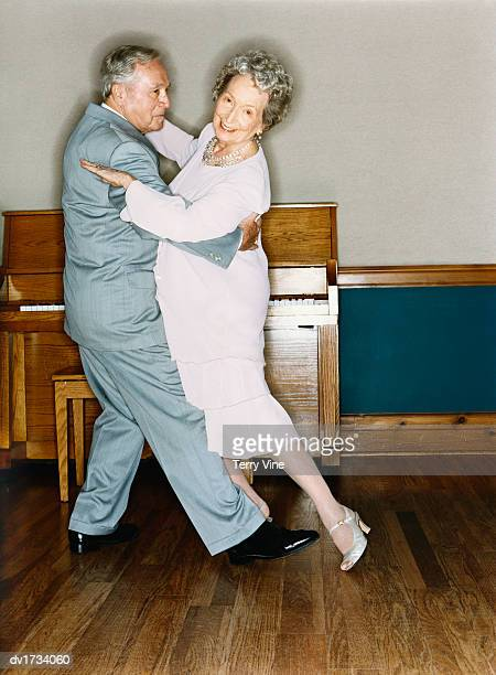Portrait of a Senior Couple Dancing in a Room with Wooden Flooring and a Piano in the Background