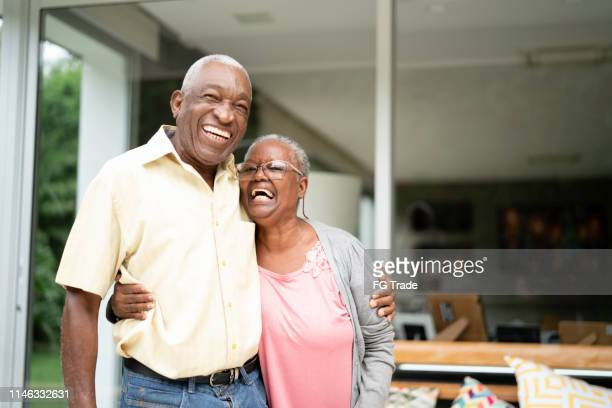 portrait of a senior couple embracing at home - active seniors stock pictures, royalty-free photos & images