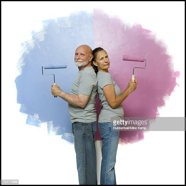 Portrait of a senior couple holding paint rollers