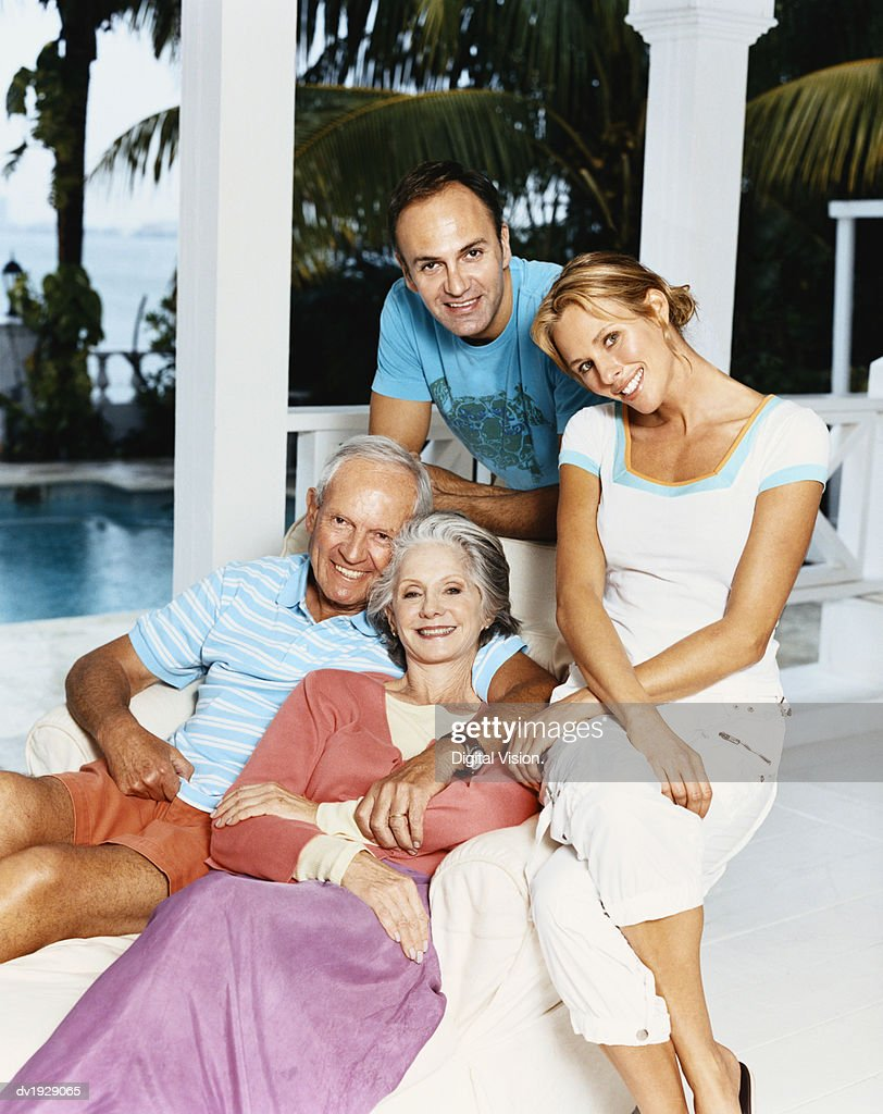 Portrait of a Senior Couple Sitting With Their Mature Children on a Porch : Stock Photo