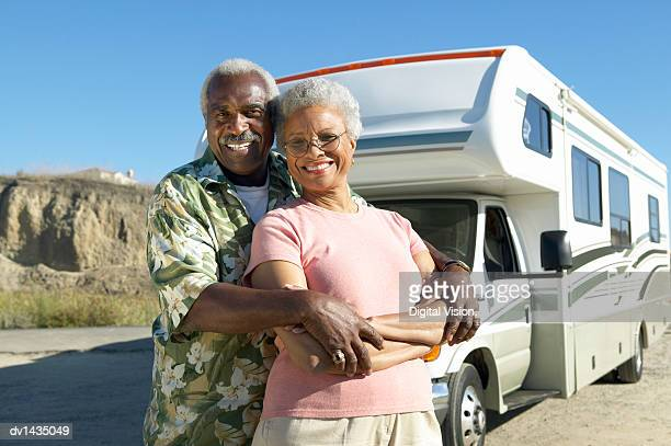 Portrait of a Senior Couple Standing in Front of Their Motor Home, Parked by a Road