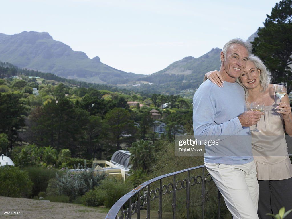 Portrait of a Senior Couple Standing on the Balcony of Their Holiday Home With a Glass of White Wine : Stock Photo