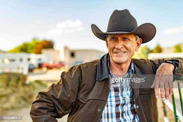 portrait of a senior cowboy on a horse ranch - rancher stock pictures, royalty-free photos & images