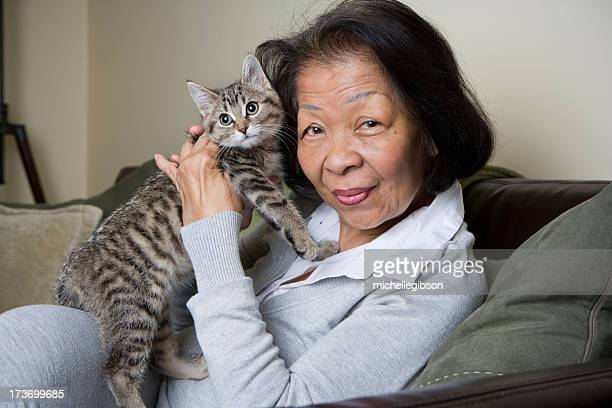 portrait of a senior elderly woman holding a kitten - undomesticated cat stock pictures, royalty-free photos & images