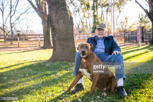 portrait of a senior farmer with his dog - patriotism stock pictures, royalty-free photos & images