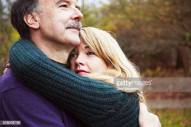 portrait of a senior father and his daughter standing in a park and embracing each other - pareja hombre mayor y mujer joven fotografías e imágenes de stock