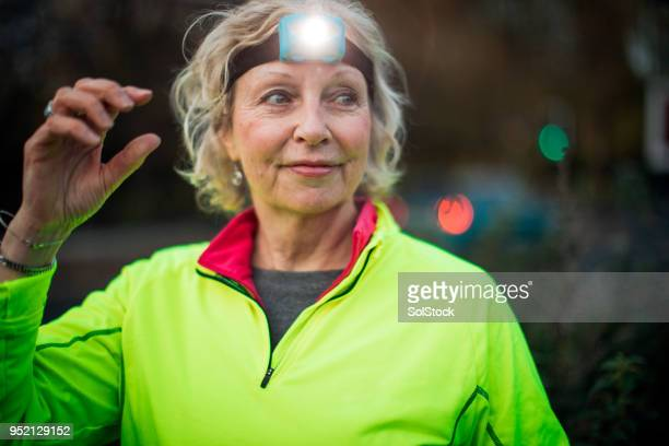 portrait of a senior female urban runner - reflective clothing stock pictures, royalty-free photos & images