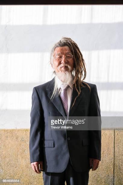 Portrait of a senior Japanese man with dreadlocks and long white beard wearing businesswear