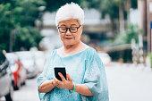 portrait senior malaysian woman with smartphone