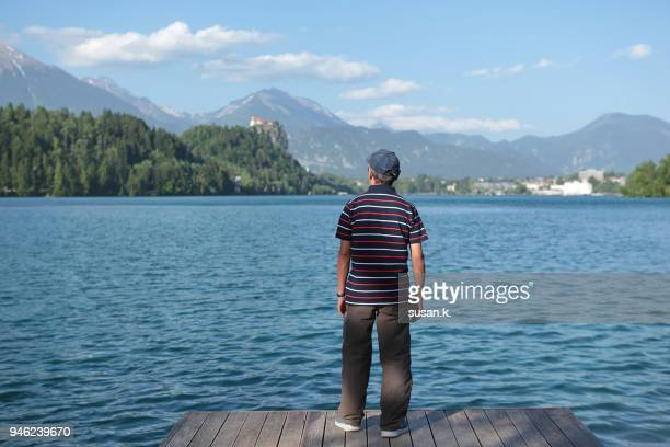 portrait of a senior man admiring beautiful lake on sunny day. - kranj stock pictures, royalty-free photos & images