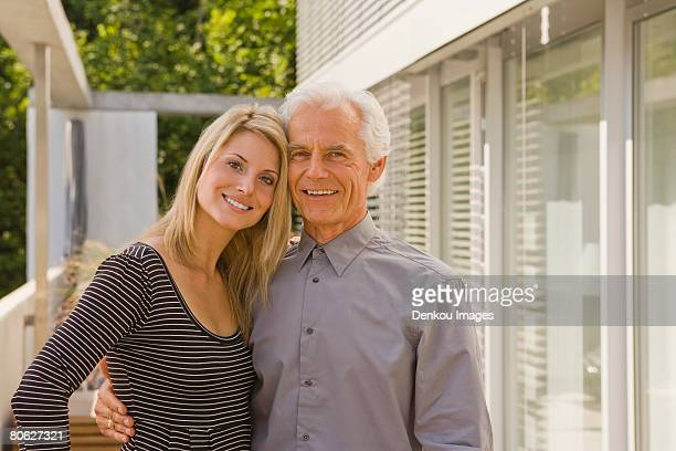 portrait of a senior man and a young woman embracing each other and smiling - may december romance stock photos and pictures