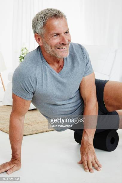 portrait of a senior man doing fascia training in his living room
