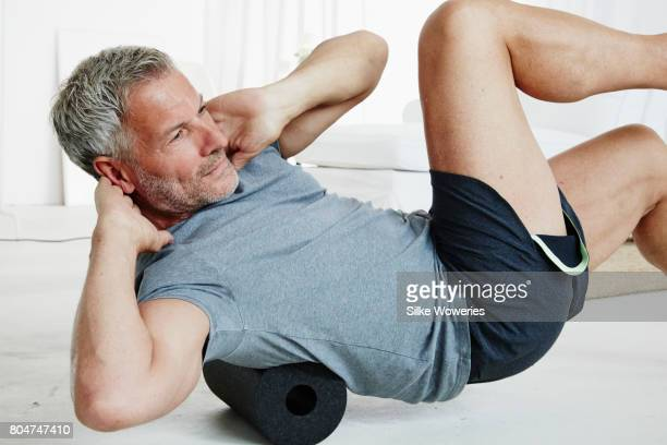 portrait of a senior man doing fascia training in his living room - trainold stock pictures, royalty-free photos & images