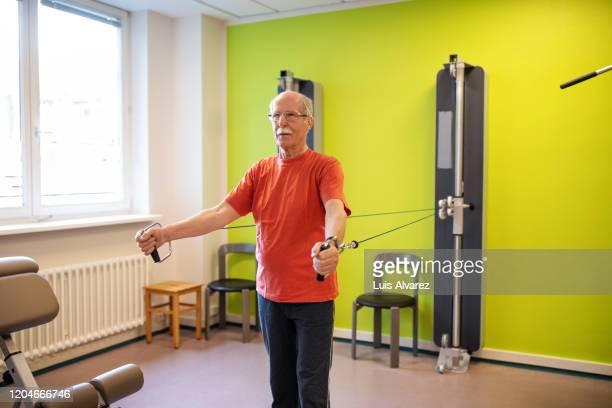 portrait of a senior man exercising at rehab center - 滑車 ストックフォトと画像