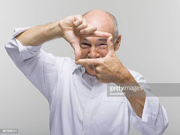 Portrait of a senior man, gesturing with one hand above the other