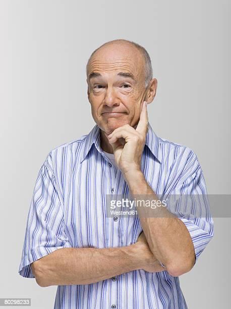 Portrait of a senior man, hand on chin, close-up