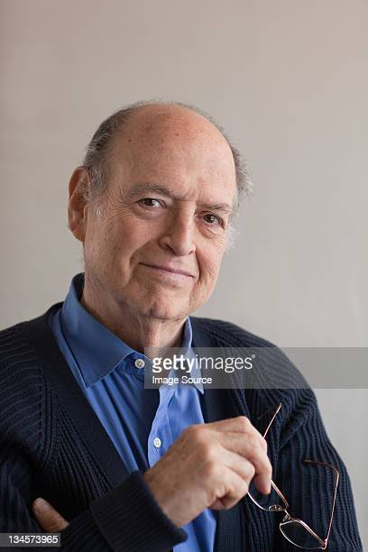 portrait of a senior man holding glasses in hand - beige background stock pictures, royalty-free photos & images