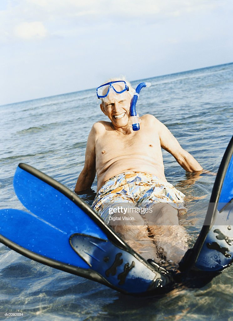 Portrait of a Senior Man in a Scuba Mask and Swimming Flippers Lying in the Sea : Stock Photo