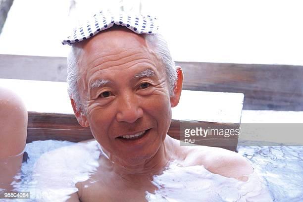 Portrait of a senior man in hot tub, smiling