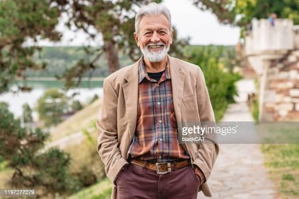 porträt eines älteren mannes im park - aktiver lebensstil stock-fotos und bilder