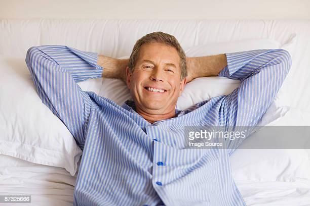 portrait of a senior man lying in bed - ナイトウェア ストックフォトと画像