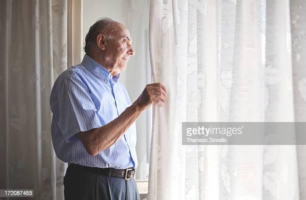 portrait of a senior man - regarder par la fenêtre photos et images de collection