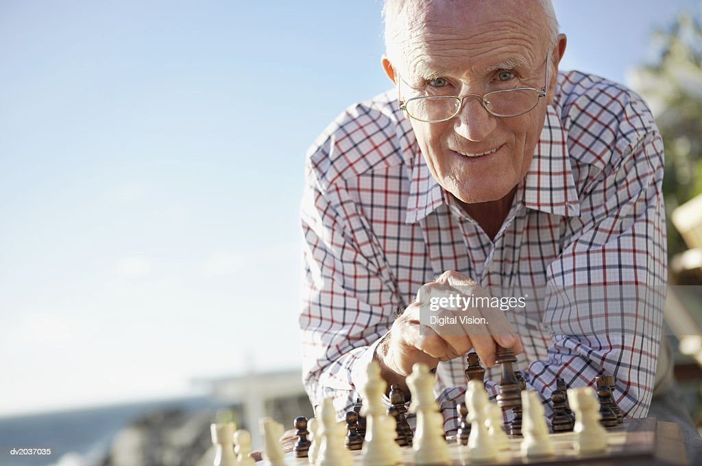 Portrait of a Senior Man Playing Chess : Stock Photo