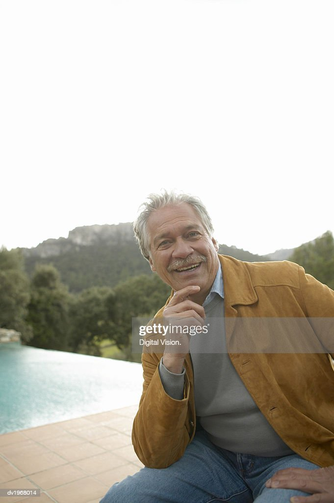 Portrait of a Senior Man Sitting by a Pool : Stock Photo