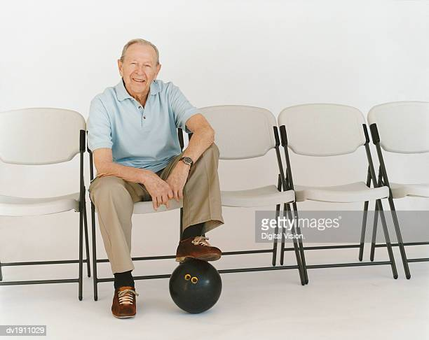 portrait of a senior man sitting on a chair with a bowling ball under his foot - old man feet stock pictures, royalty-free photos & images
