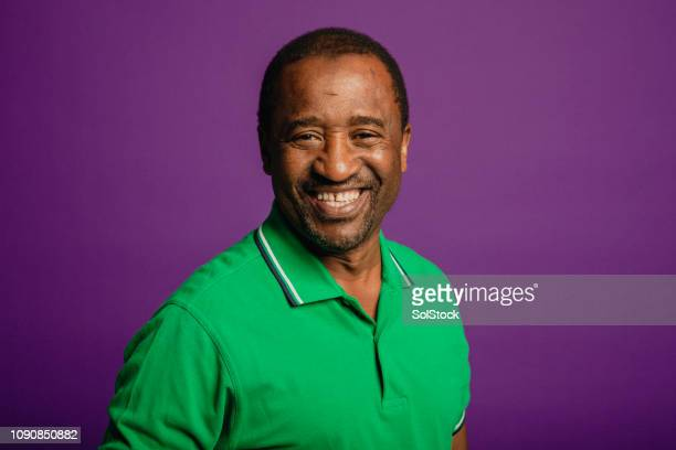 portrait of a senior man smiling at camera - purple background stock photos and pictures