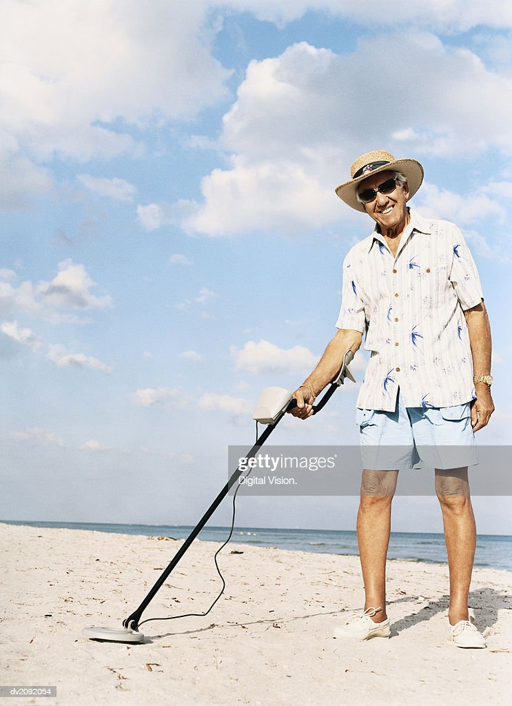 Portrait of a Senior Man Standing on a Beach Holding a Metal Detector : Stock Photo