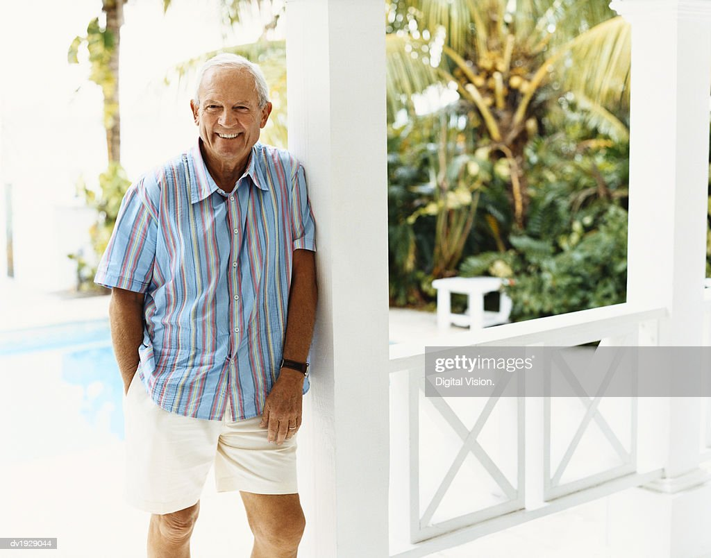 Portrait of a Senior Man Standing on a Porch in Summer : Stock Photo