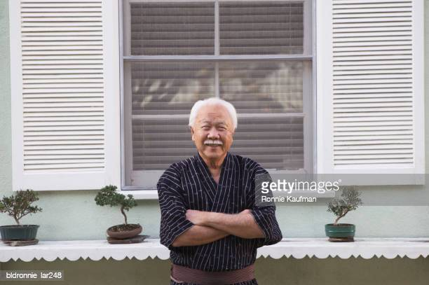 portrait of a senior man standing with his arms crossed - one man only stock pictures, royalty-free photos & images