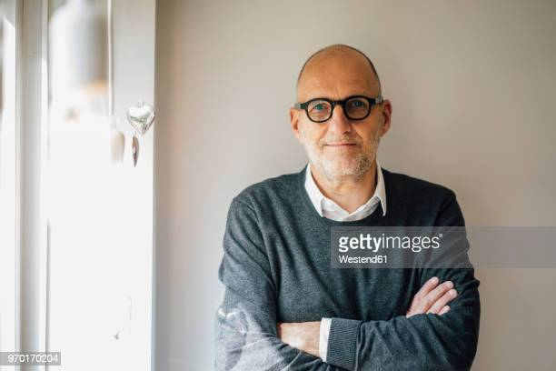portrait of a senior man, staning in front of wall with arms crossed - mann 60 jahre stock-fotos und bilder
