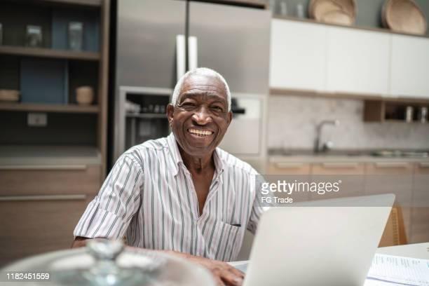 ritratto di un uomo anziano che usa il laptop nel tavolo della cucina - uomini anziani foto e immagini stock