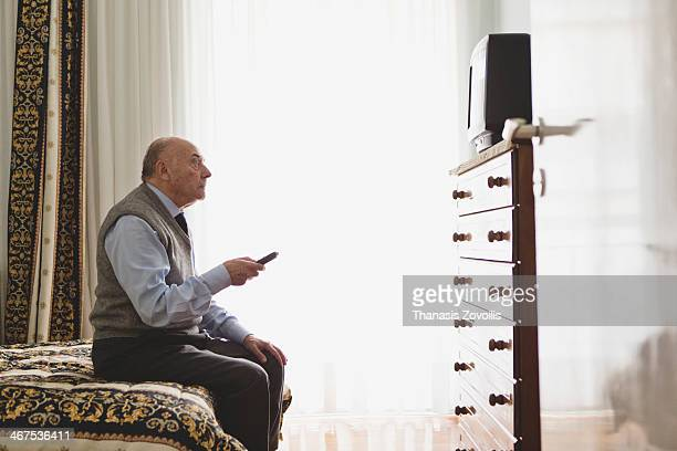 Portrait of a senior man watching television