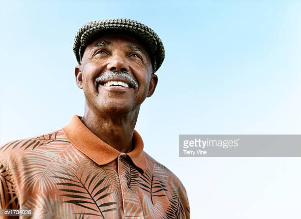 portrait of a senior man wearing a cap and floral print shirt - blue hat stock pictures, royalty-free photos & images