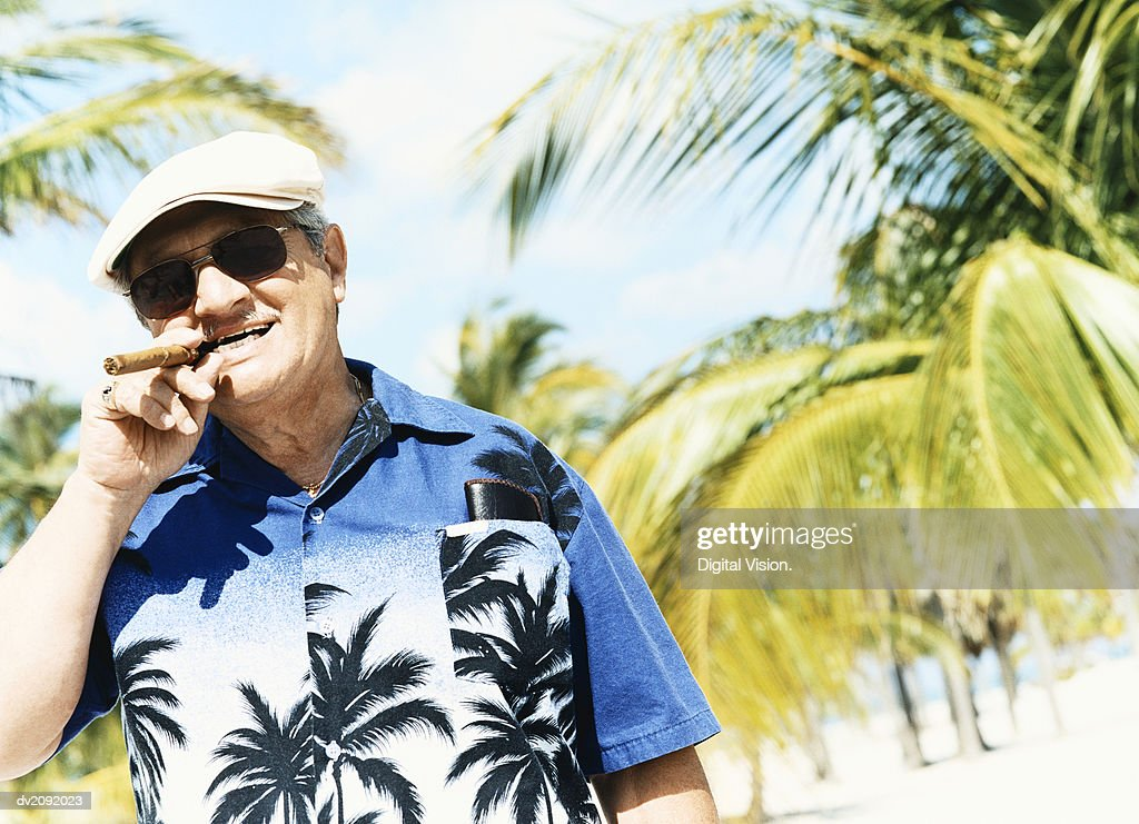 Portrait of a Senior Man Wearing a Hawaiian Shirt and Smoking a Cigar, with Palm Trees in the Background : Stock Photo