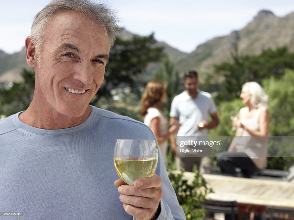 Portrait of a Senior Man With Glass of White Wine and a Group of People Standing Outdoors in the Background : Stock Photo