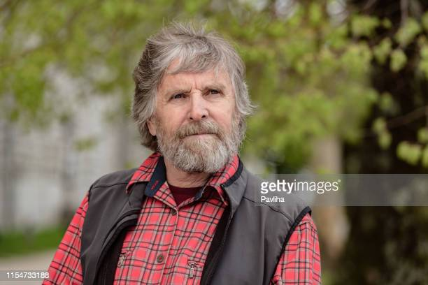 portrait of a senior man with gray beard in europe - windbreak stock pictures, royalty-free photos & images