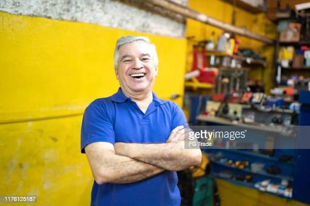 retrato de um mecânico sênior que está com os braços cruzados em uma auto loja de reparo - pequeno - fotografias e filmes do acervo