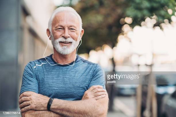 portrait of a senior sportsman with arms crossed - white hair stock pictures, royalty-free photos & images