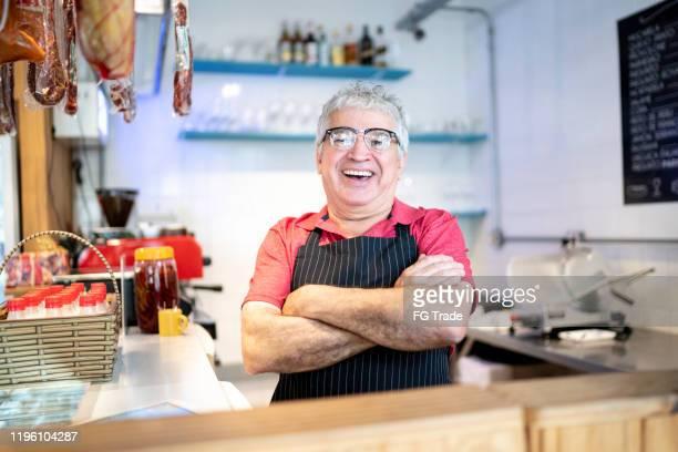 portrait of a senior waiter / butcher in a butcher's shop of a supermarket - butcher's shop stock pictures, royalty-free photos & images