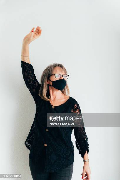 a portrait of a senior woman 50-55 years old wearing a black colored mask , smiling and dancing. - 55 59 years stock pictures, royalty-free photos & images
