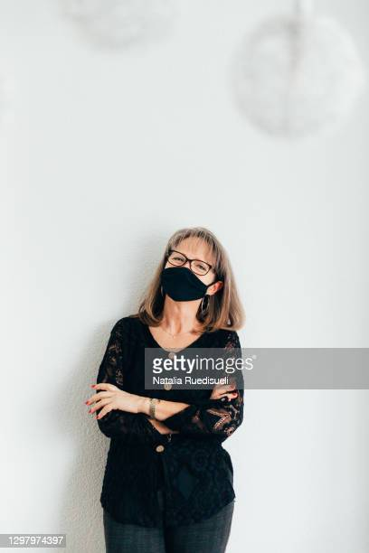 a portrait of a senior woman 50-55 years old wearing a mask and smiling into the camera. - 55 59 years stock pictures, royalty-free photos & images
